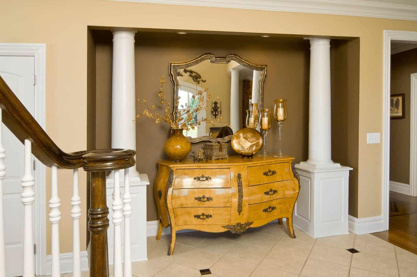 A wooden console table with mirror and brass decors is situated inside the inset wall in this foyer lined with a pair of white columns.