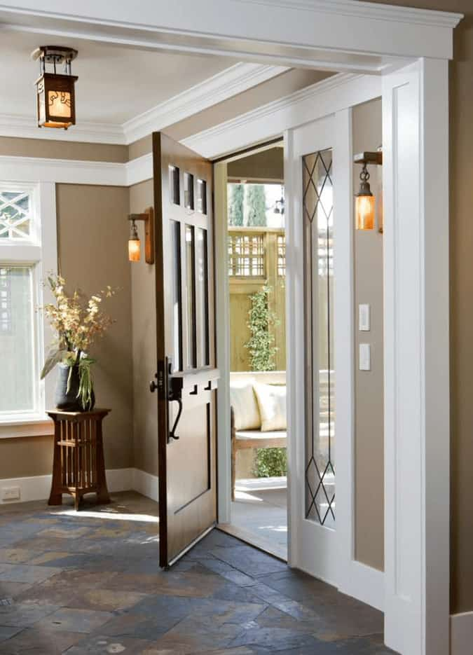 Wooden wall sconces illuminate this foyer along with a pendant light that hung from the tray ceiling. It has rustic flooring and a natural wood entry door lined with glass panels.