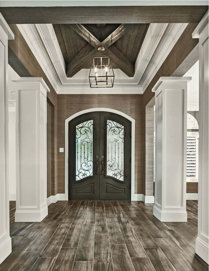Traditional foyer framed with white columns and illuminated by a caged pendant that hung from the wood beam tray ceiling.