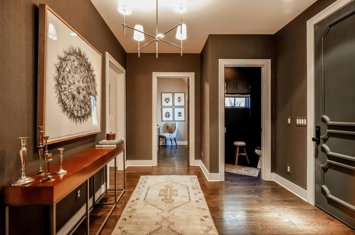 The transitional foyer features a contemporary chandelier and a metal console table that's accented with a huge framed wall art mounted on the brown wall.