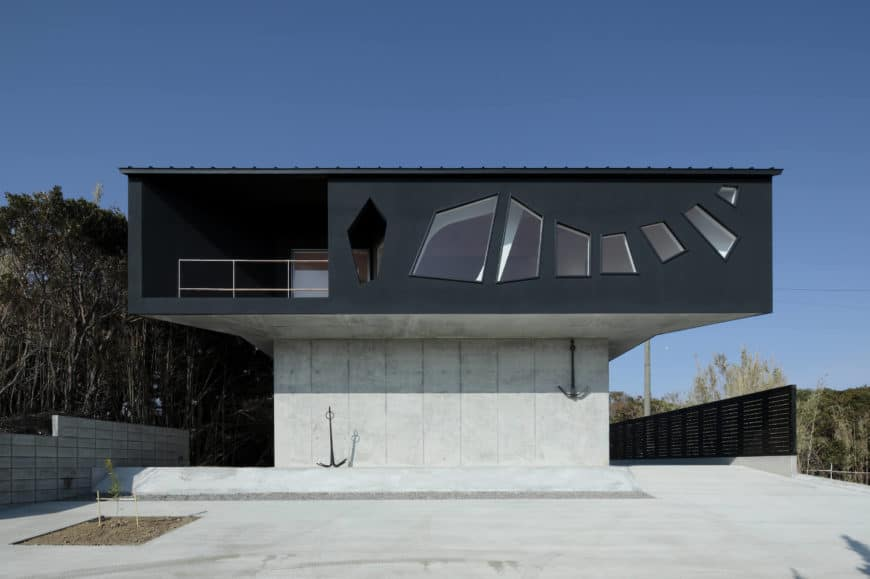 Large modern house with a concrete exterior finished in black. Its exterior has a very stylish design as well.