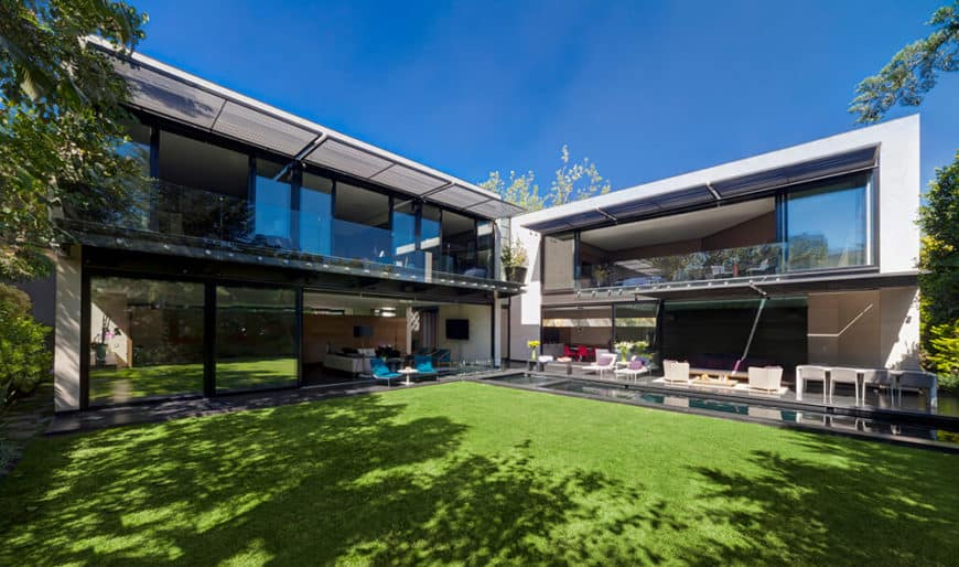This contemporary home offers a wide backyard with a lawn area and a small swimming pool.