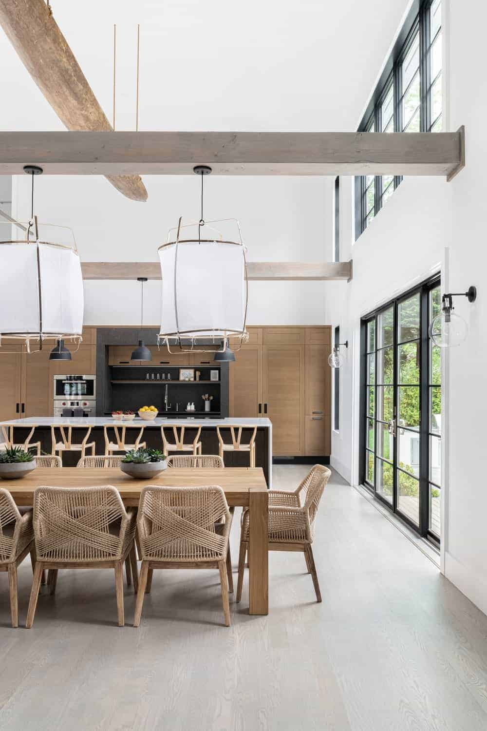 The dining room is surrounded by the white walls and white tall ceiling. The area features a wooden rectangular dining table set.