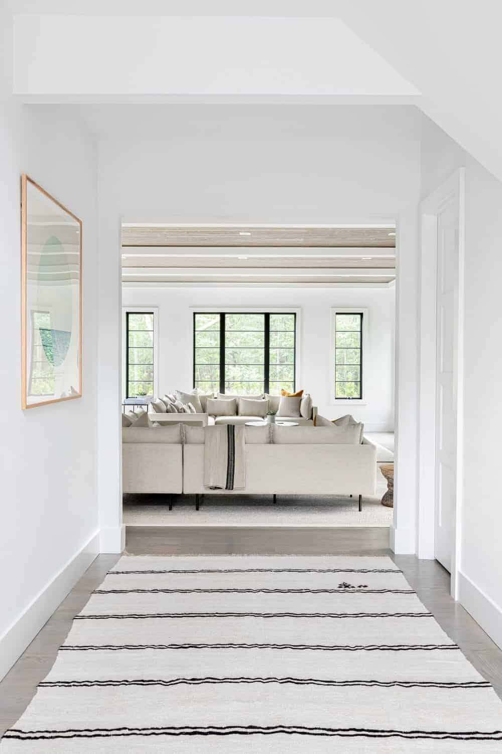 A hallway leading to the home's living room, featuring white walls and a stylish area rug.