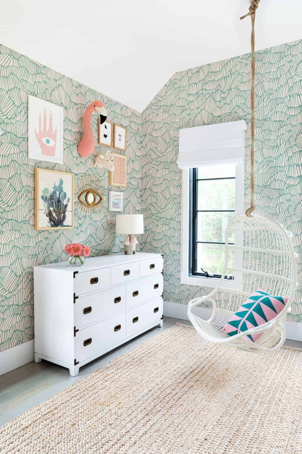 The kids bedroom boasts charming green walls along with a white ceiling and a large brown area rug.