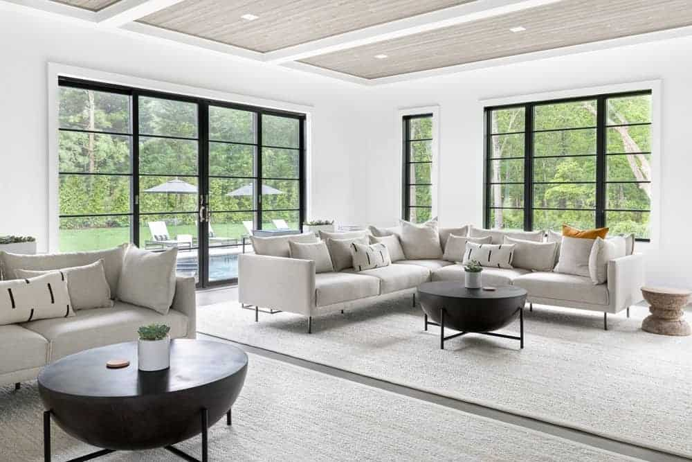 This living room features modern sofa sets along with a pair of center table, surrounded by white walls, glass mirrors and doors.