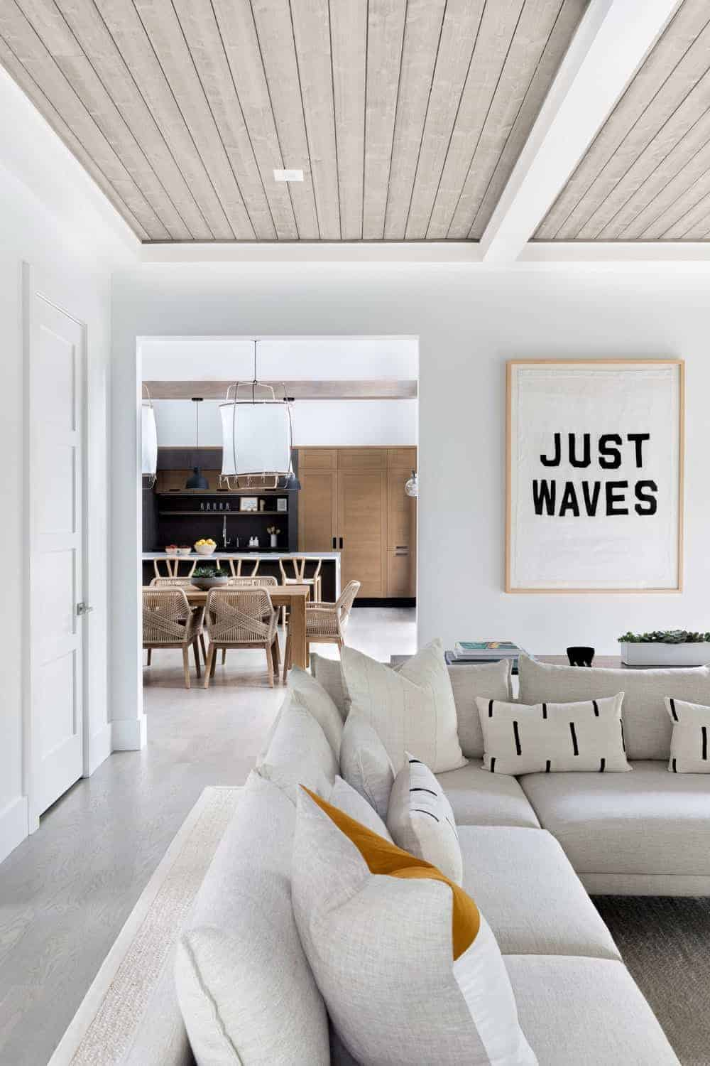 The living room features wooden ceiling with concrete beams along with white walls surrounding the area.