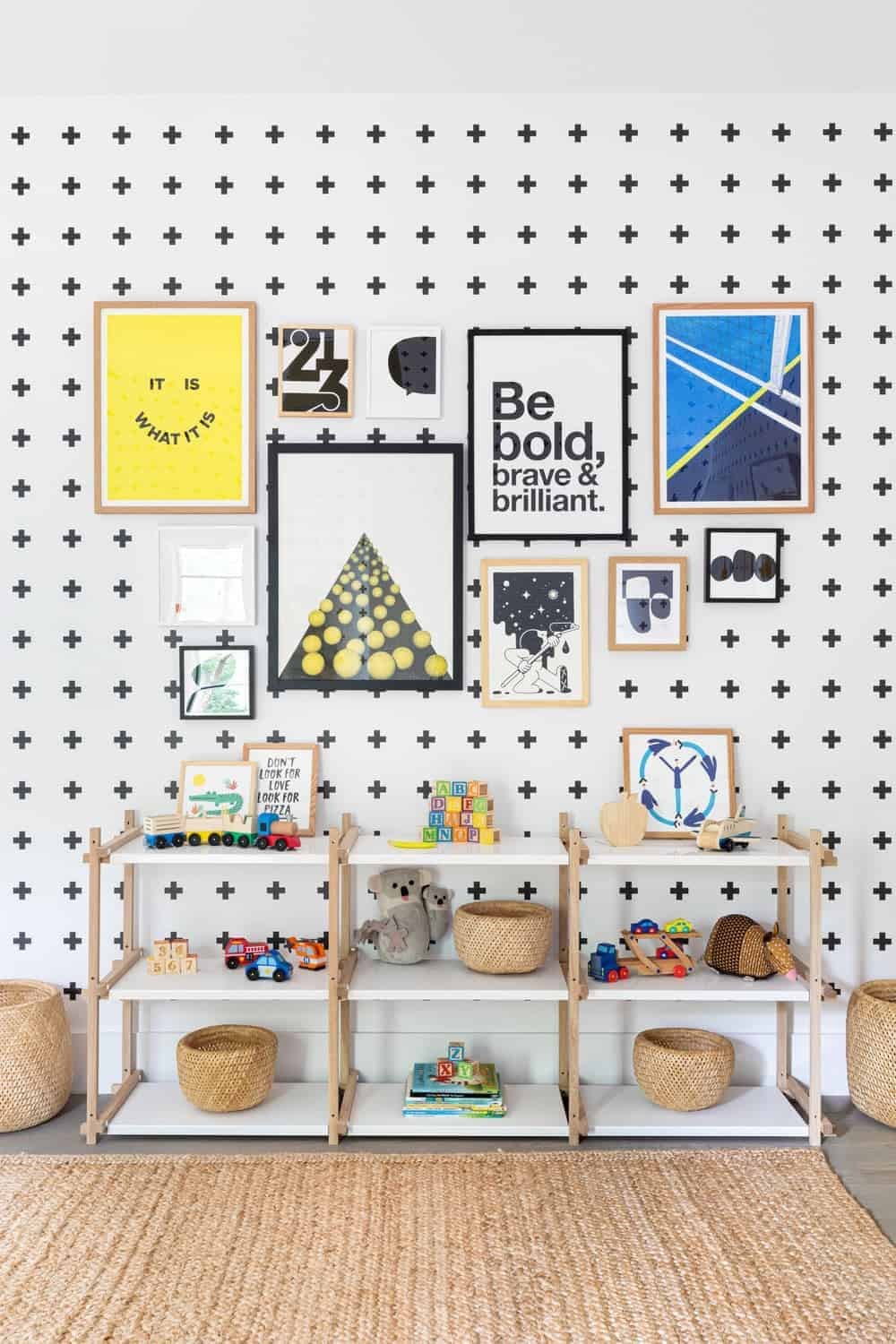 A focused look at the nursery room's multiple wall decors and freestanding short shelving.