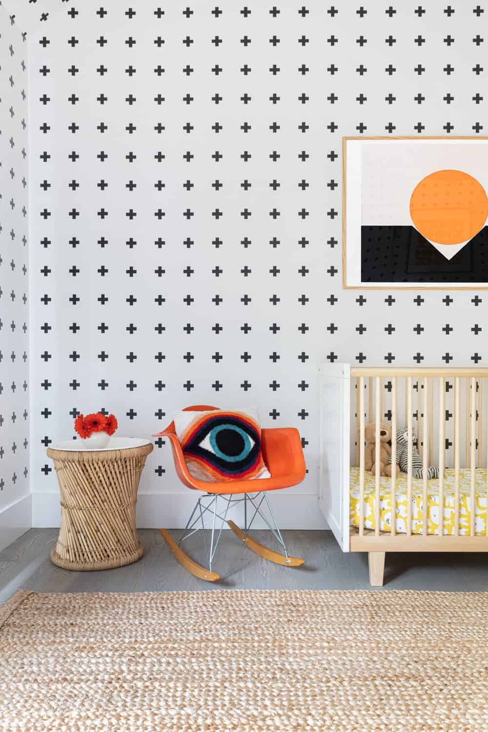 This nursery room features stylish wall design and a large area rug covering the gray hardwood flooring.