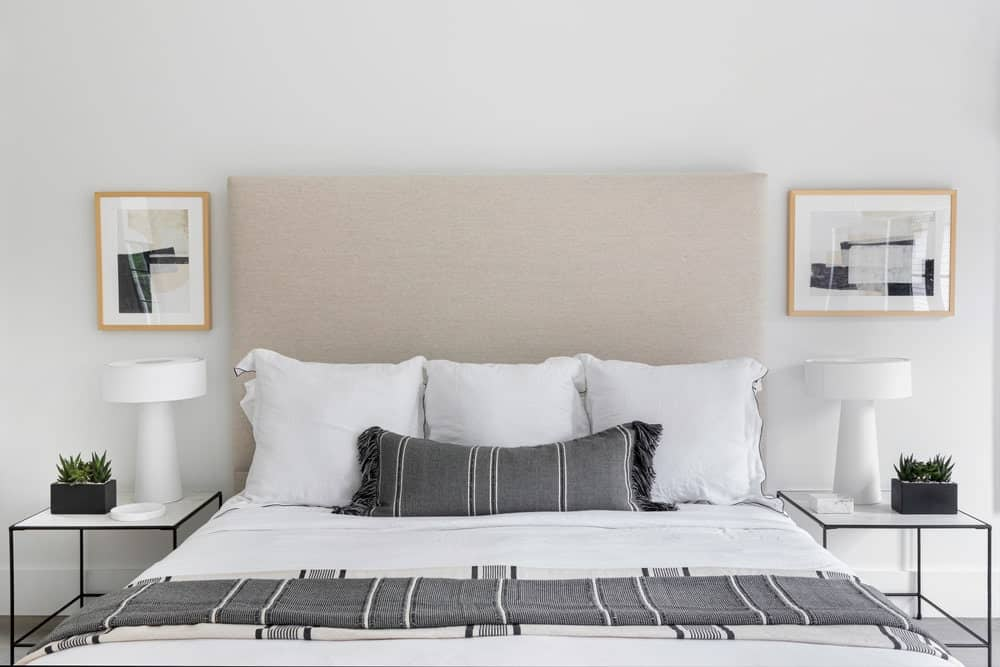 A close up look at the master bedroom's large modern bed with white and gray color scheme and has two side tables both with table lamps.