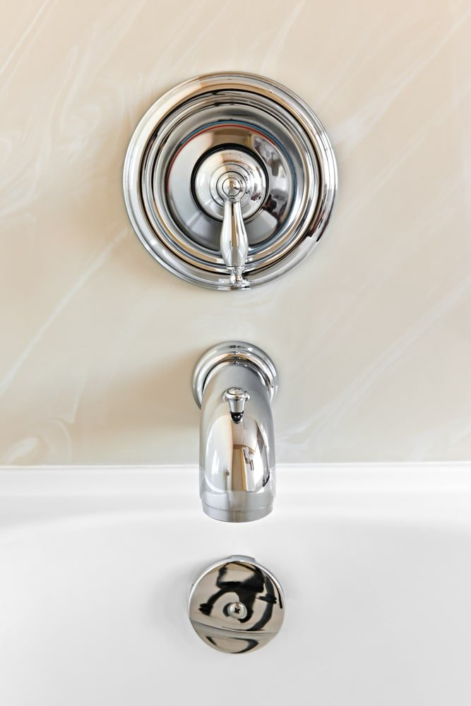 This is a close look at a chrome finish bathroom faucet by the bathtub.