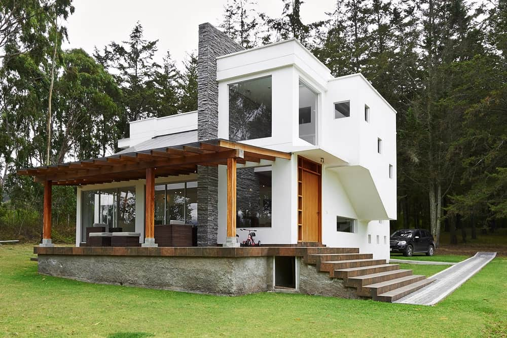 Contemporary house exterior surrounded by pine trees.