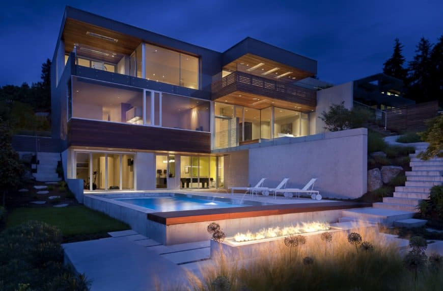 A large contemporary home featuring a swimming pool with multiple sitting lounges on the side. There's a fire pit area as well.