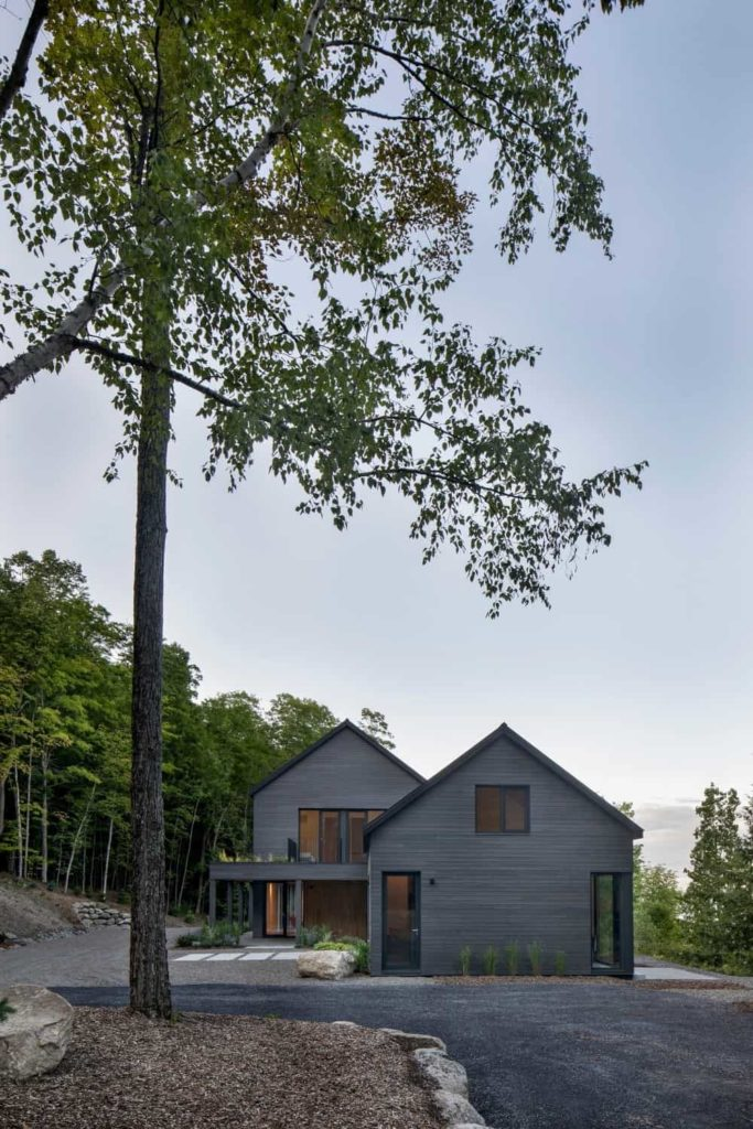This is a charming Contemporary-style home that has an isolated and peaceful landscape filled with tall trees and rocks lining the asphalt driveway towards the wooden house with gable roof. The hue of this home exterior makes it part of the landscape.