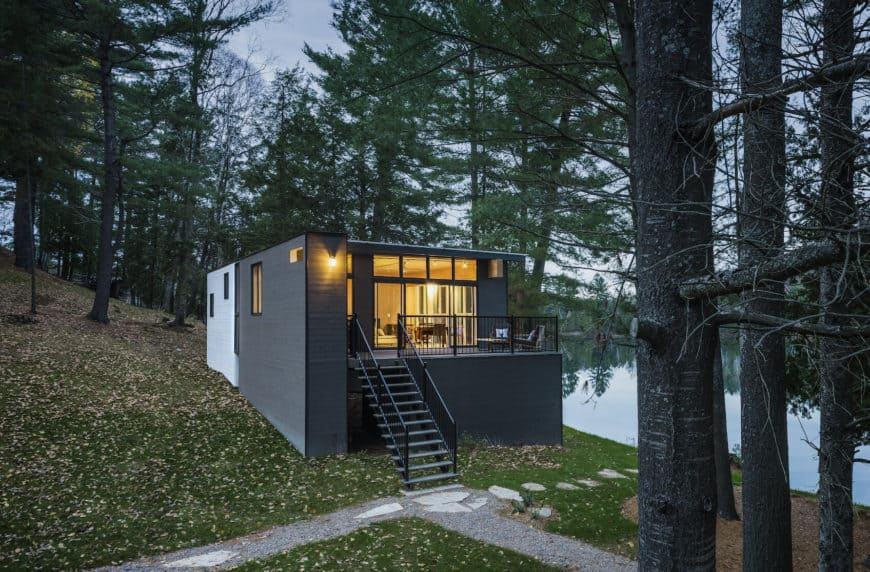 A timber cottage house finished in black and has a terrace that offers a breathtaking view of the surroundings and the lake.