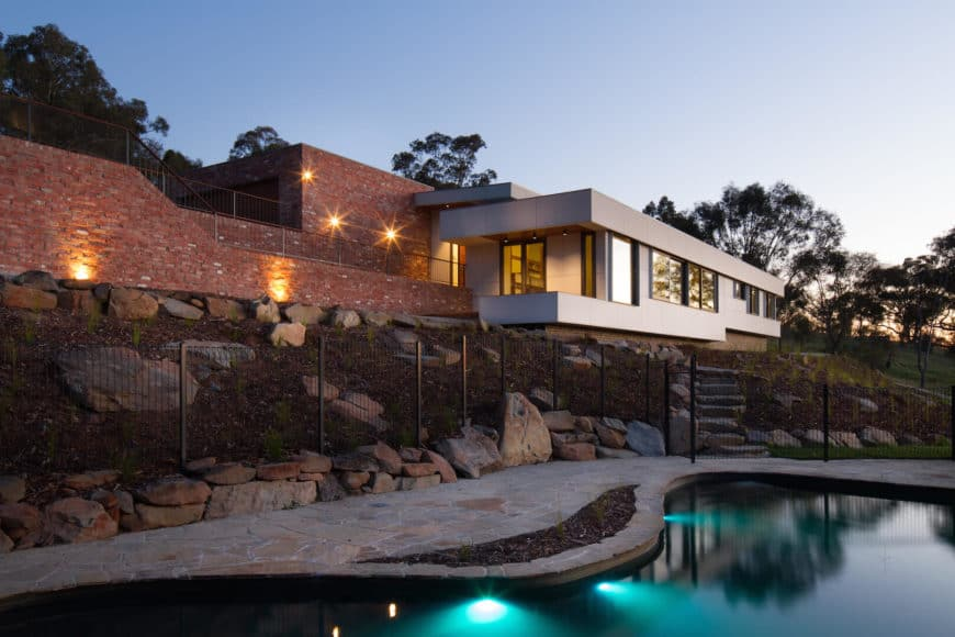 A custom split-level family contemporary home with a beautiful swimming pool outside.