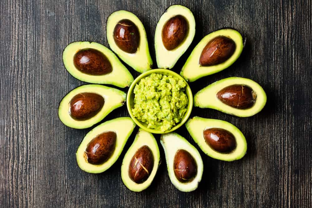 Cut Avocados Surrounding a Bowl of Guacamole