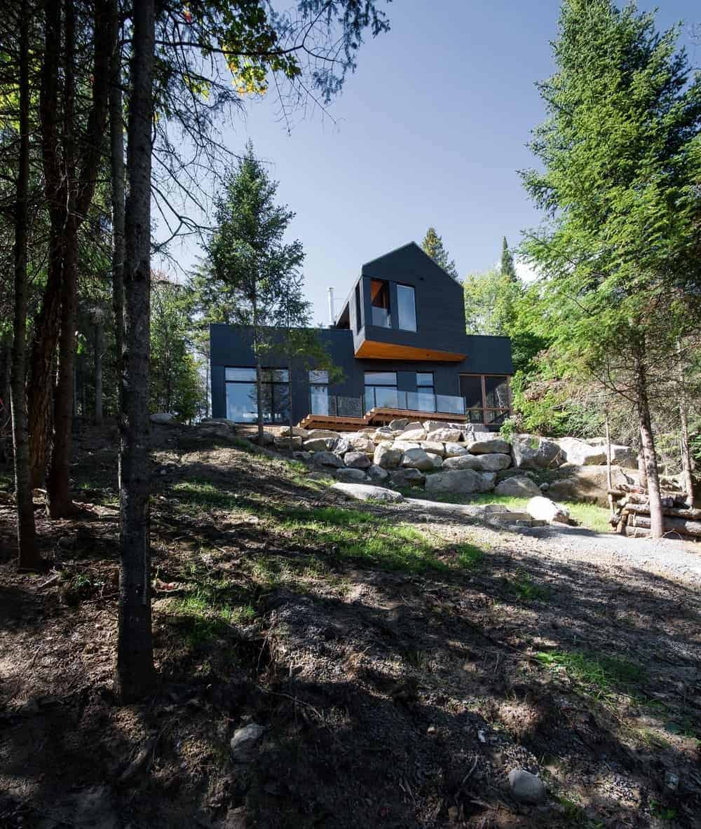 This modern home with a black exterior sits in the middle of the woods, and is surrounded by mature trees.