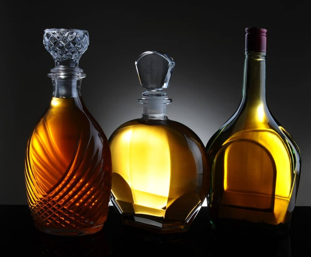 Three different types of decanters in a dark background.