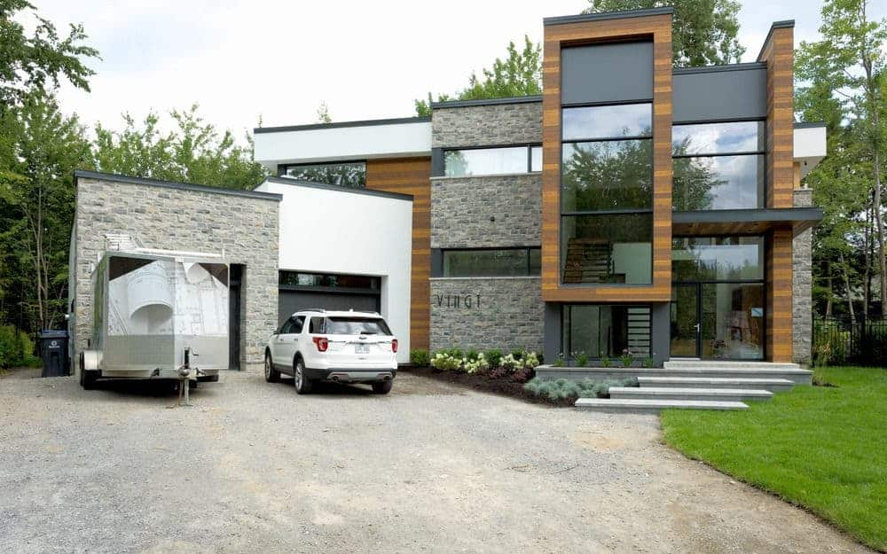 A contemporary house featuring a wide driveway and a well-maintained lawn area.