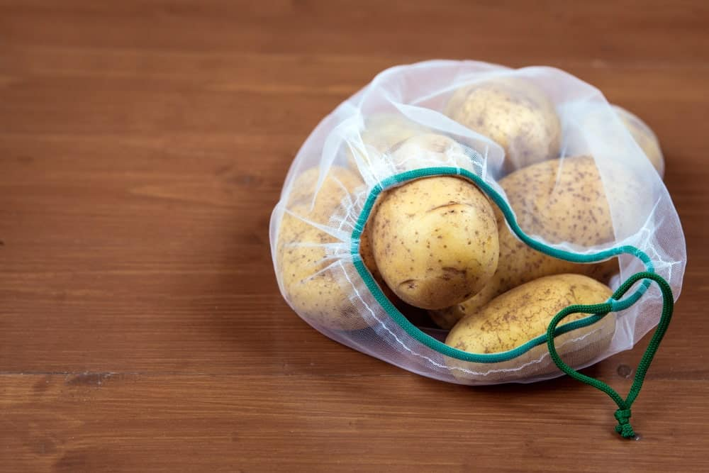 Potatoes in an eco bag on a wooden desk.