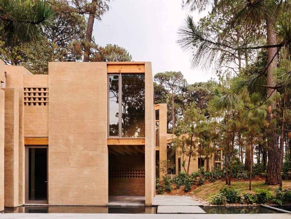 A large contemporary house with a beige exterior and is surrounded by tall trees.