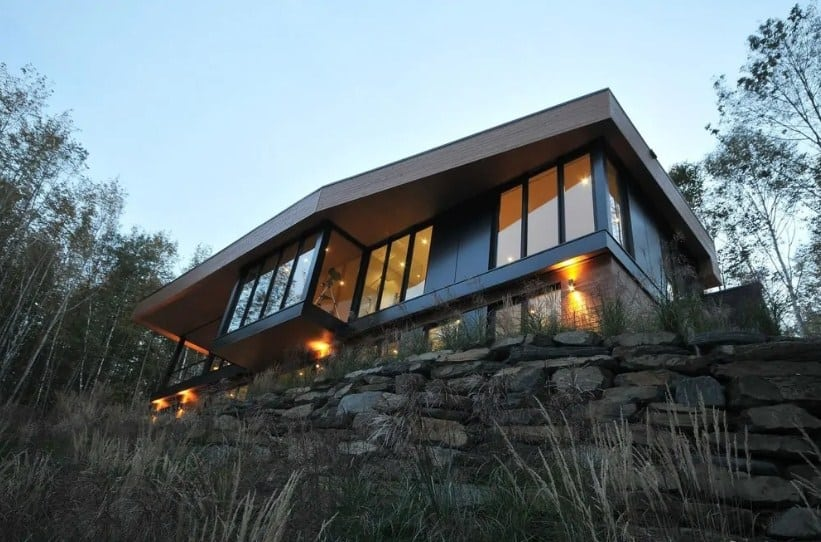 A large modern home with a black exterior and is set on stones, also surrounded by mature trees.