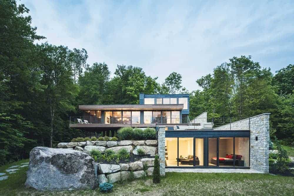 This contemporary house is situated in the middle of the woods and is surrounded by mature trees.