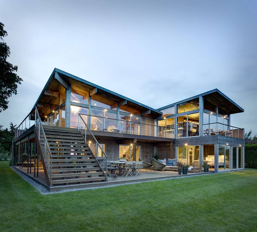 This contemporary home features glass walls and windows along with a wide lawn area.