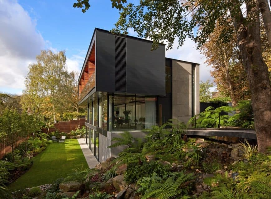 A contemporary house with a beautiful backyard featuring a well-maintained lawn area and a gorgeous garden.
