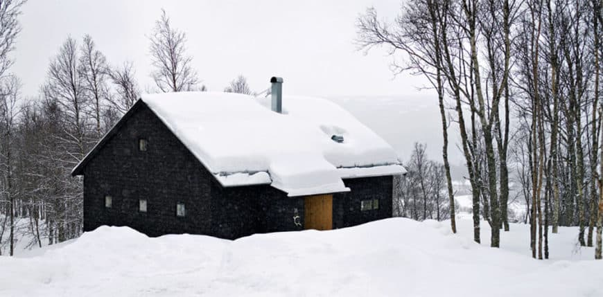 This mountain home features a black exterior and is covered in snow.