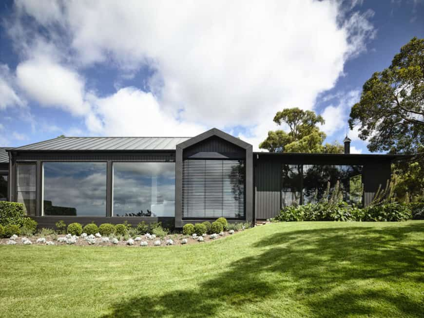 A custom home with a black exterior and has a sprawling lawn and garden areas.