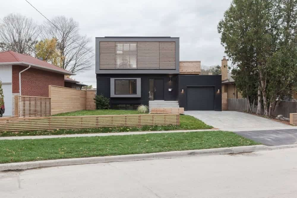 A modern house with a black exterior, a driveway with a garage and a lawn area.