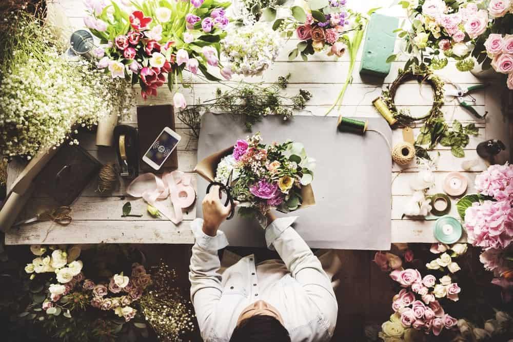 Top view of a florist working on a bouquet or flower arrangement.