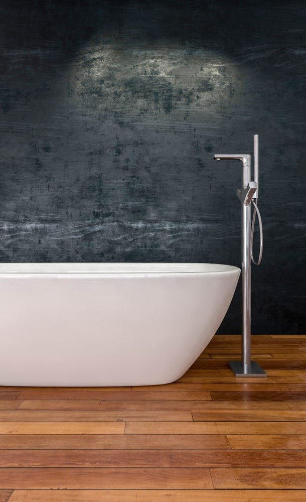 A freestanding tub faucet at the head of the freestanding bathtub that stands out against the dark wall and dark hardwood flooring.