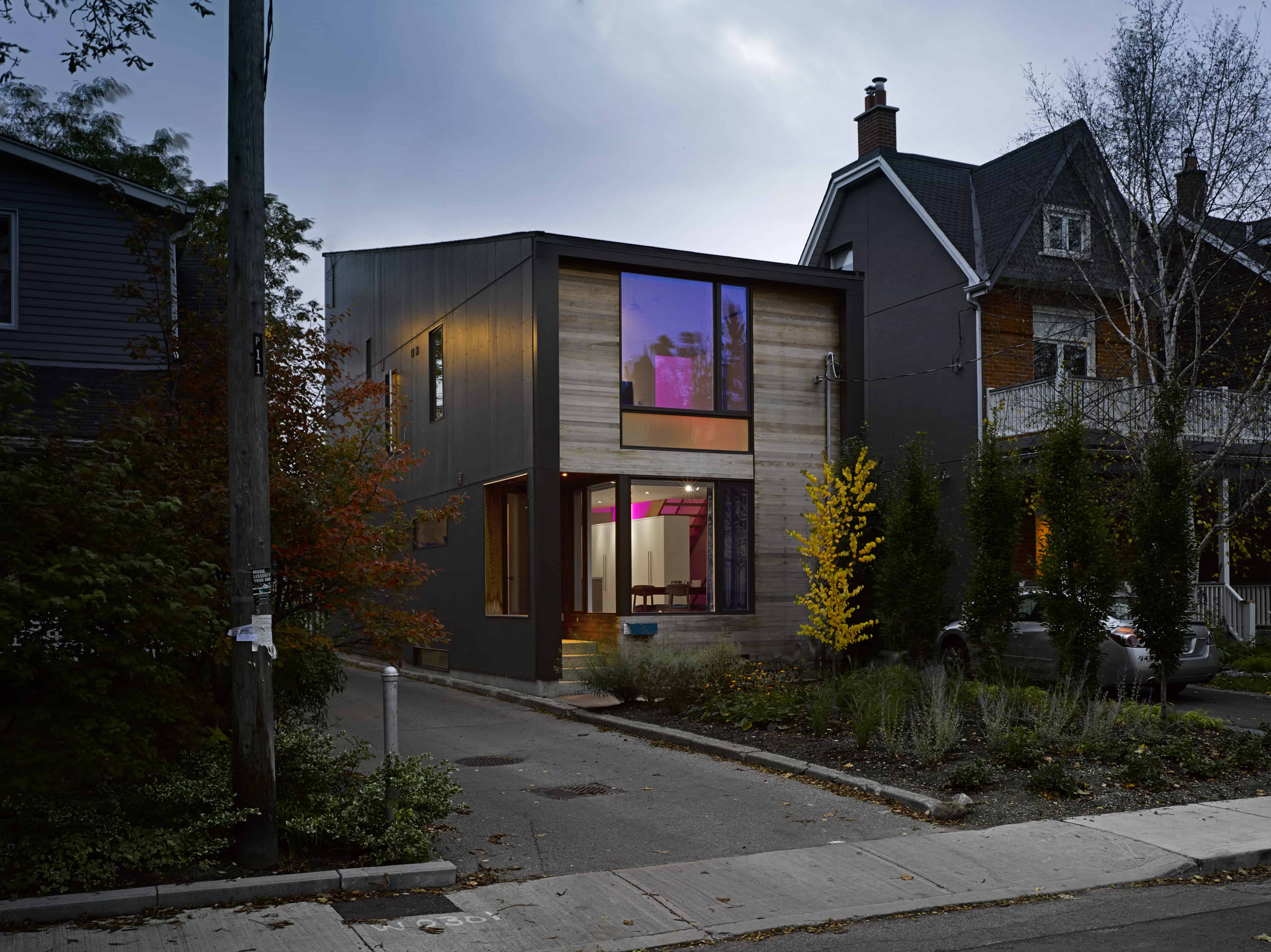 Modern house with a black exterior along with a small garden area.
