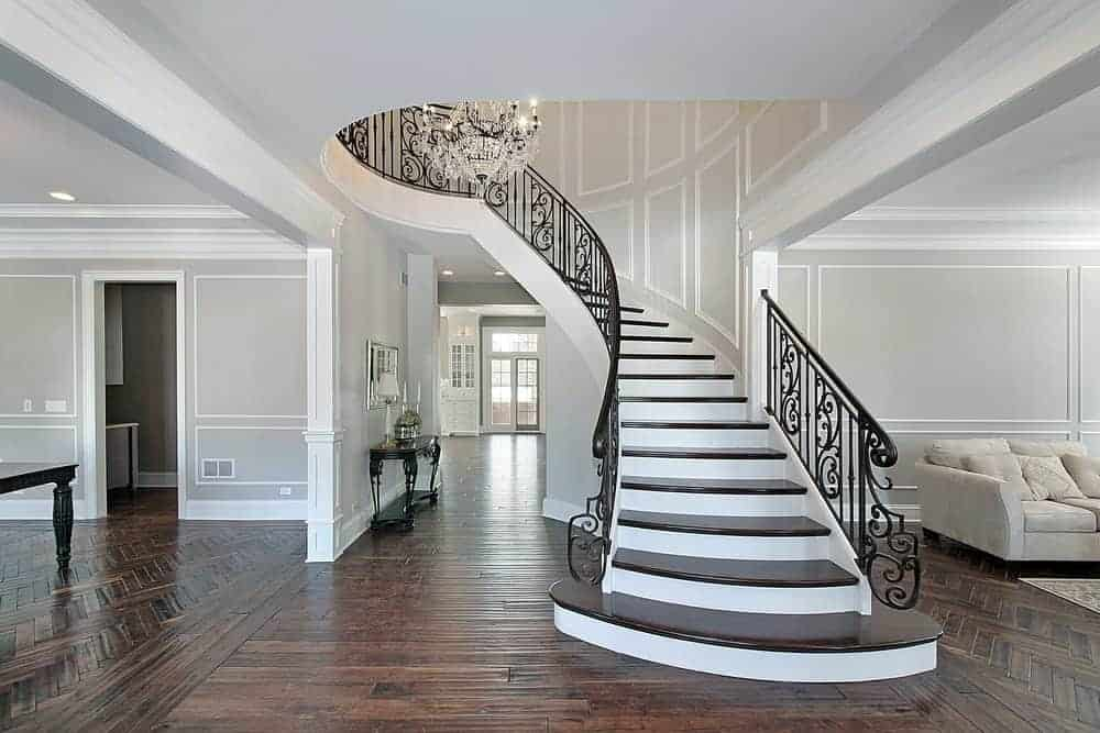 This foyer features gray walls with a white accent. The area has hardwood floors and a staircase with iron railings.