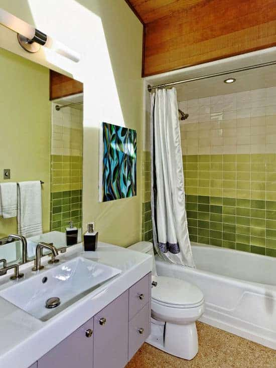 The walls of the bathtub and shower area of this bathroom have green tiles fixed into a fading color pattern that matches well with the artwork mounted over the toilet.