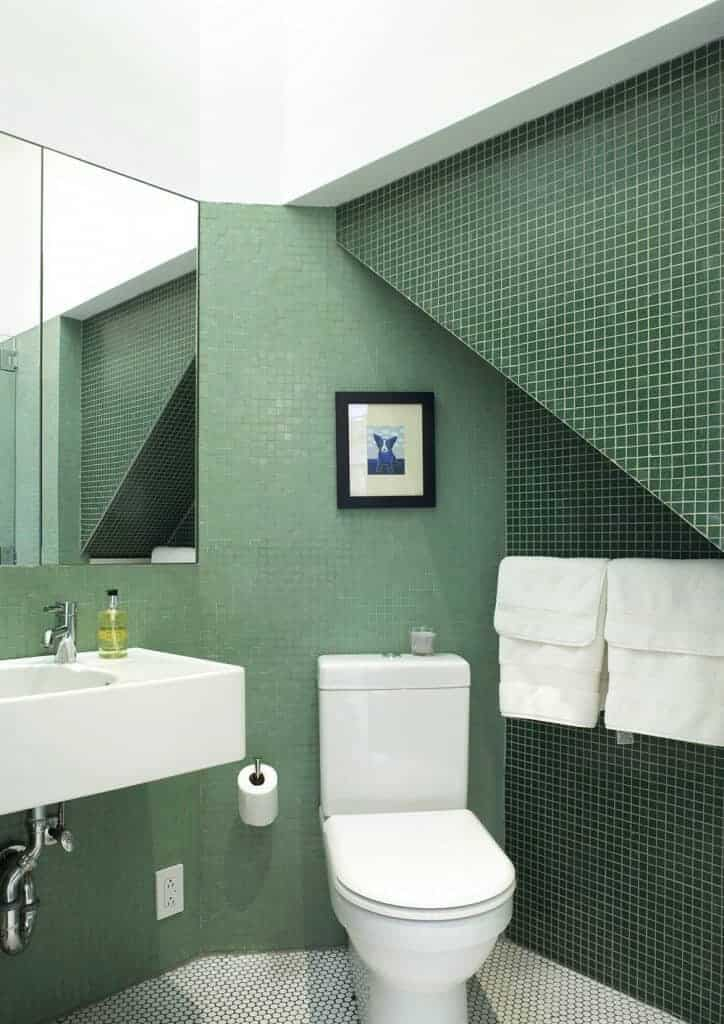 This is an under-the-stairs bathroom with uneven walls covered with small green tiles of varying hues that make the toilet and sink stand out.