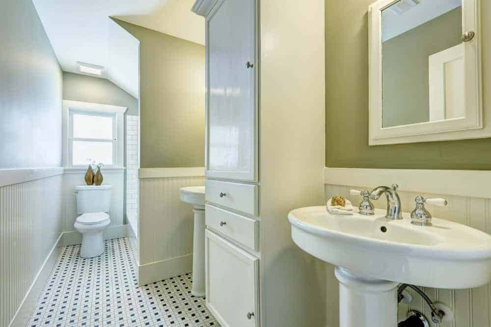 The light green hues of this bathroom is further brightened by the natural light coming in from the window above the toilet. The patterend tiles of the floor contradict with the striped finish of the lower half of the walls.