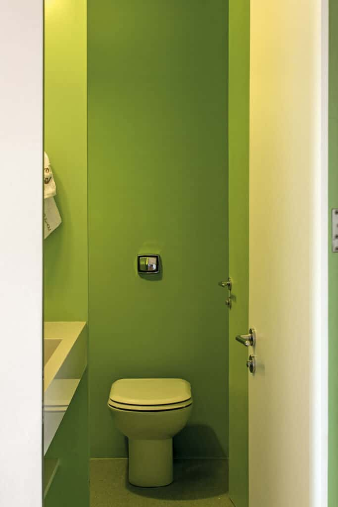 This is an outside view of the bathroom that has simple apple green walls unadorned and matches with the back-less toilet.
