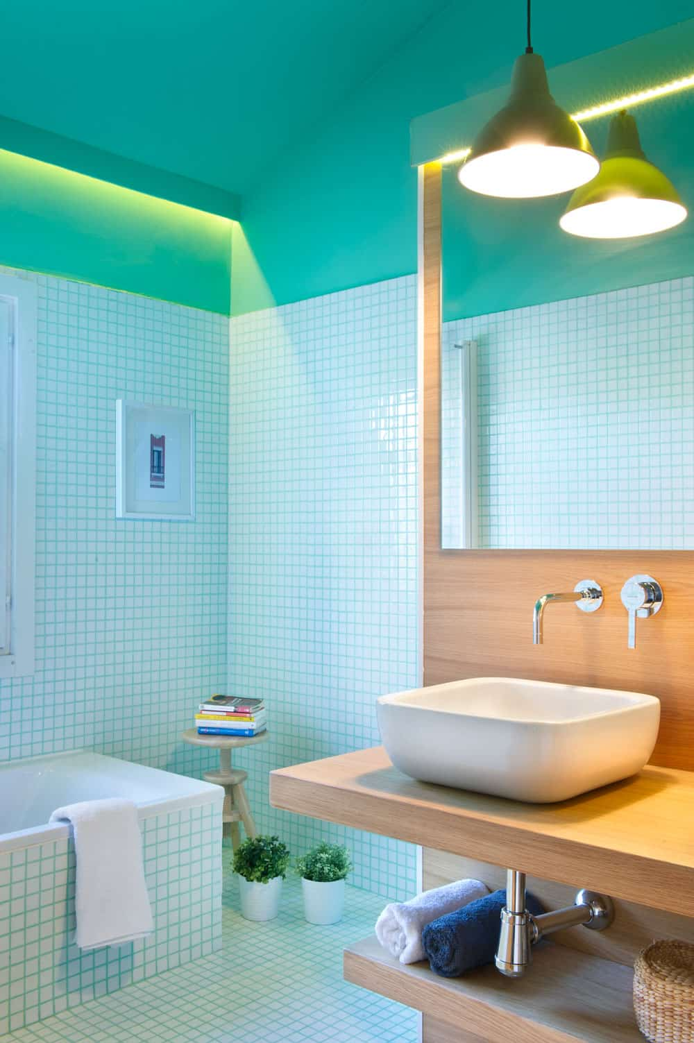 This room has a lovely shade of green above the tiled walls and flooring that is outlined with grout of the same hue as the wall.
