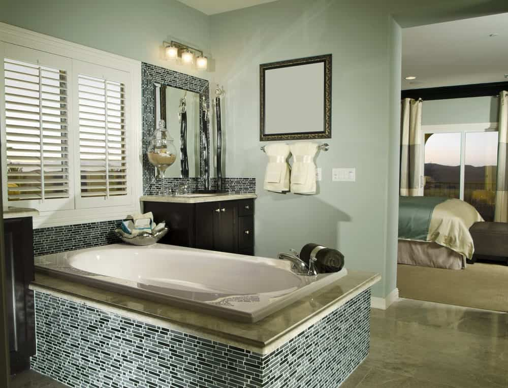 The gorgeous bathtub is inlaid with a beige marble countertop and green tiles on the sides that extend to the backsplash of the vanity. This works well with the light green walls.