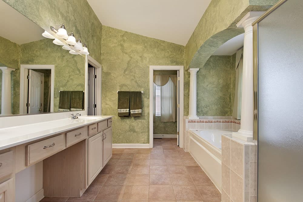 The green walls have a lovely dynamic design that works well with the beige flooring and the long vanity topped with a massive mirror. The vanity area mirrors the bathtub area.