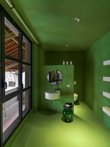 This is a spacious bathroom with uniform green walls, floor, and ceiling adorned with modern recessed lights and huge glass windows.