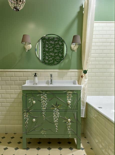 The green vanity drawers are adorned with orchid artwork that gives a chic quality to the green-walled bathroom.