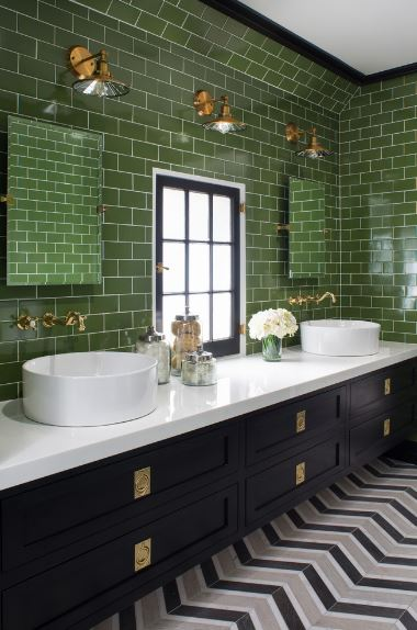 This two-sink vanity area has a white countertop that contrasts the green-tiled walls and the dark drawers.