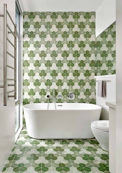The clover-like green patterns of the tiles dominate the flooring and walls behind the freestanding bathtub.