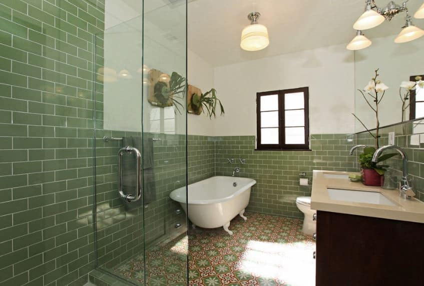 The patterned tiles of the flooring are matched with green-tiled walls that make the freestanding bathtub pop out.