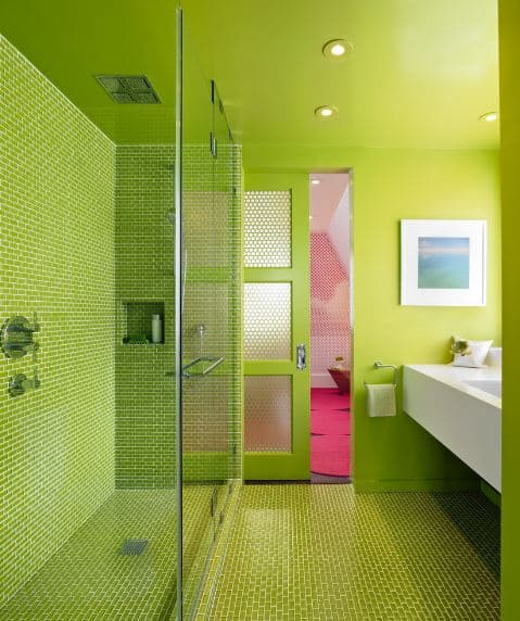 The flooring of this bathroom is made up of small green tiles that extend to the shower room that is separated from the rest of the bathroom by a glass wall.